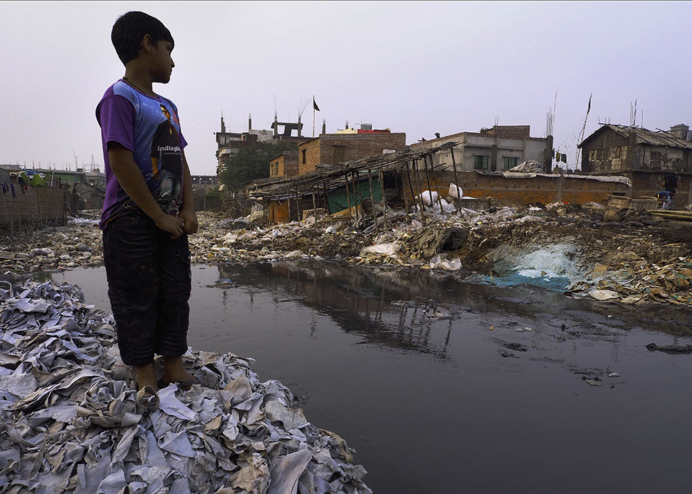 A boy stands on a pile of leather scraps beside a canal in the Hazaribagh neighborhood of Dhaka, Bangladesh. Waste and chromium-laden effluent from unregulated leather tanneries have made Hazaribagh one of the most intensely polluted places on Earth.